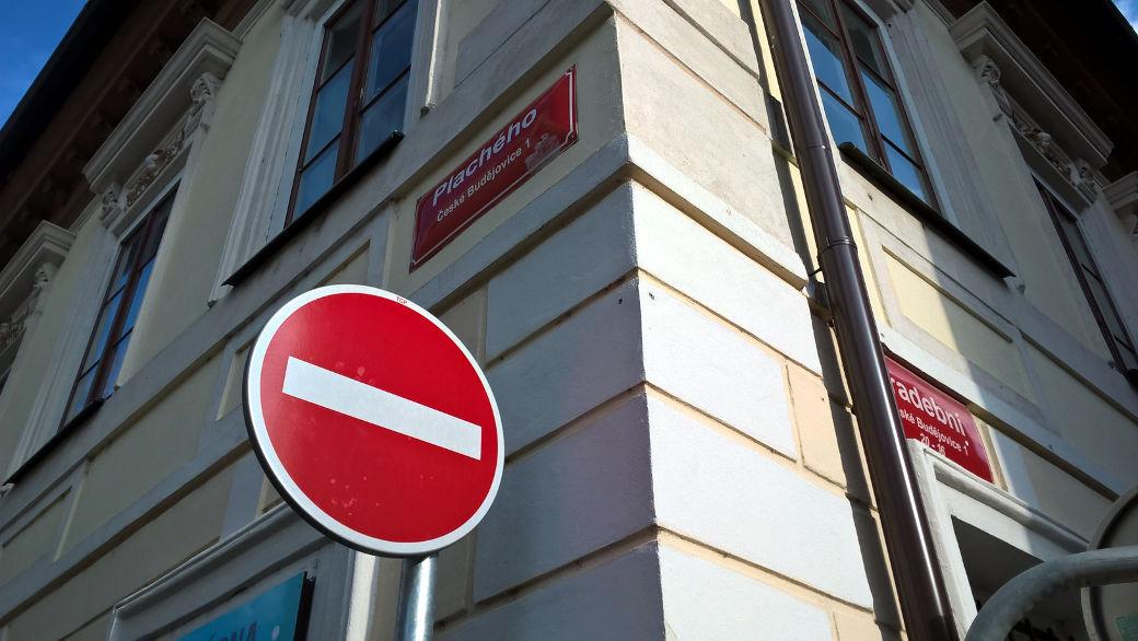 Dobře známá příkazová značka zákaz vjezdu všem vozidlům a názvy ulic - psané bíle na červeném pozadí (České Budějovice)